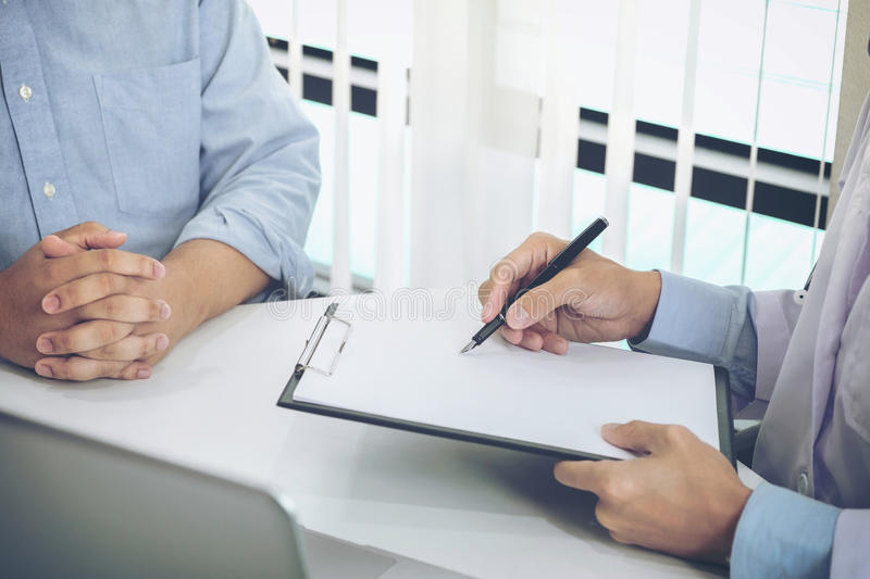 Close up of doctor filling up an history form while consulting p stock image