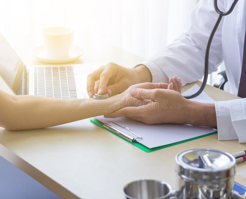 Close up of doctor hand reassuring her female patient at hospital. Closeup hands of medical doctor carefully holding patient royalty free stock photos