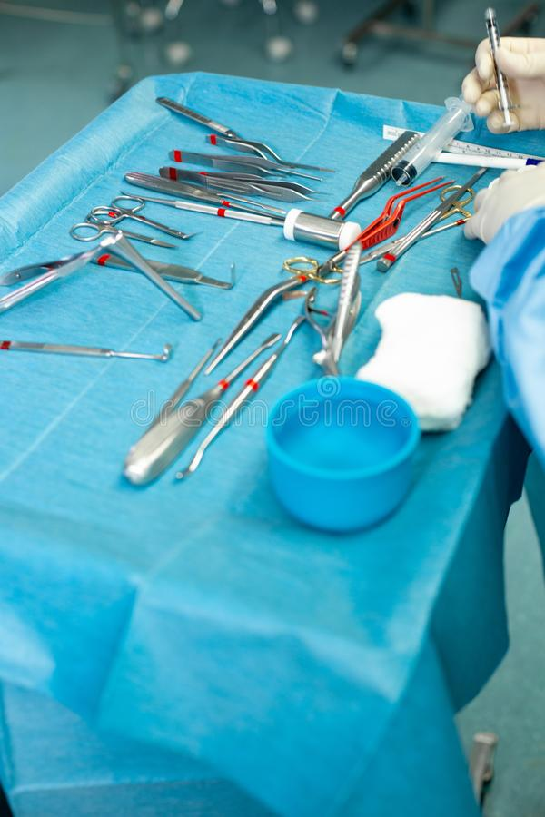 Close up of doctor hands during surgery in operation room. Sterile surgery instruments used in a real operation. Focus. Is on the row of clamp handles stock image