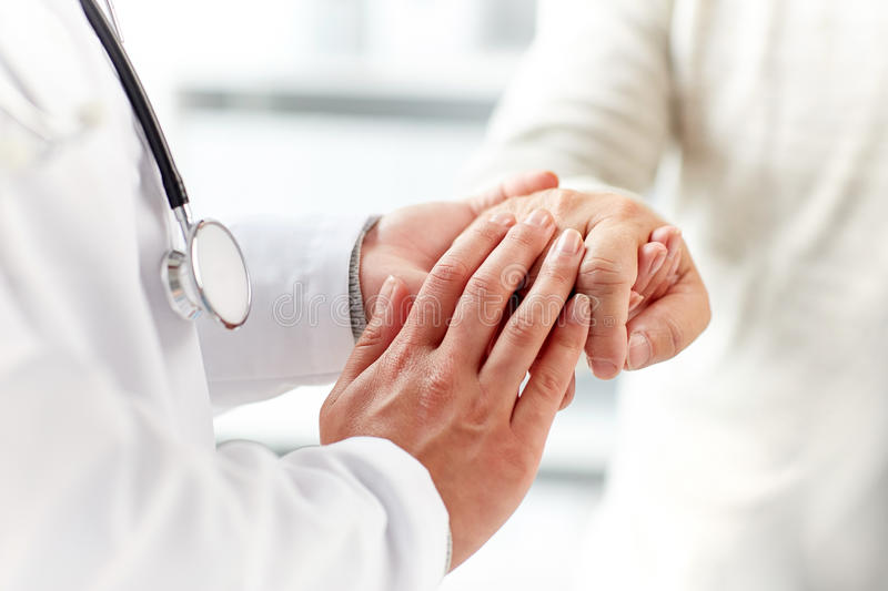 Close up of doctor holding old man hand royalty free stock image