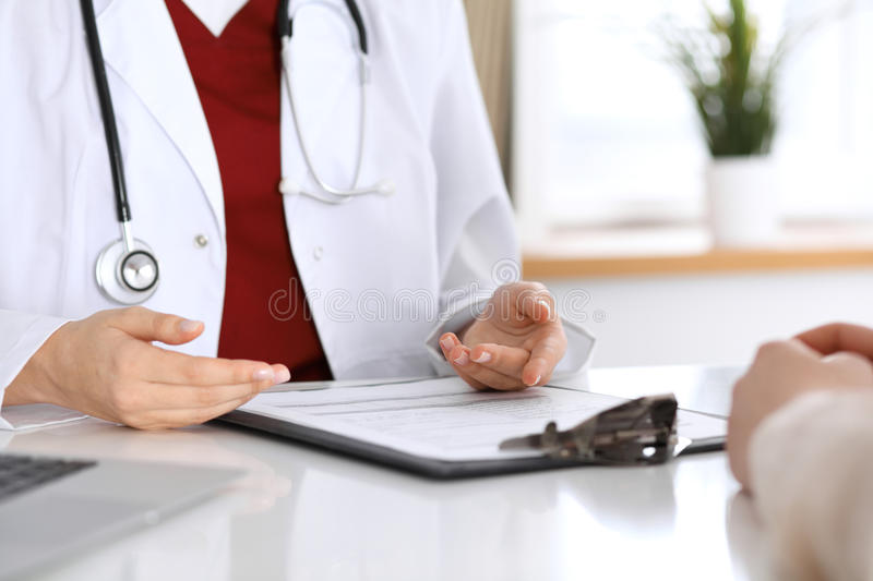 Close up of a doctor and patient hands while discussing medical records after health examination royalty free stock image