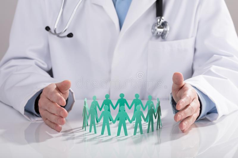 Doctor Protecting Paper Cut Out Figures On Desk. Close-up Of A Doctor`s Hand Protecting Blue Paper Cut Out Figures On Desk royalty free stock images