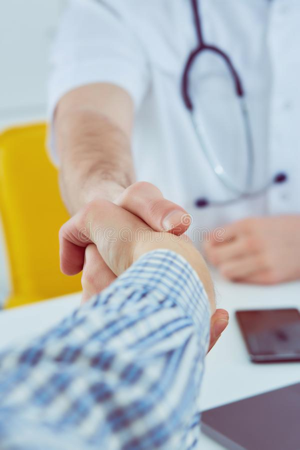 Close up of a male doctor shaking hands with his male patient. Medicine and trust concept royalty free stock photo