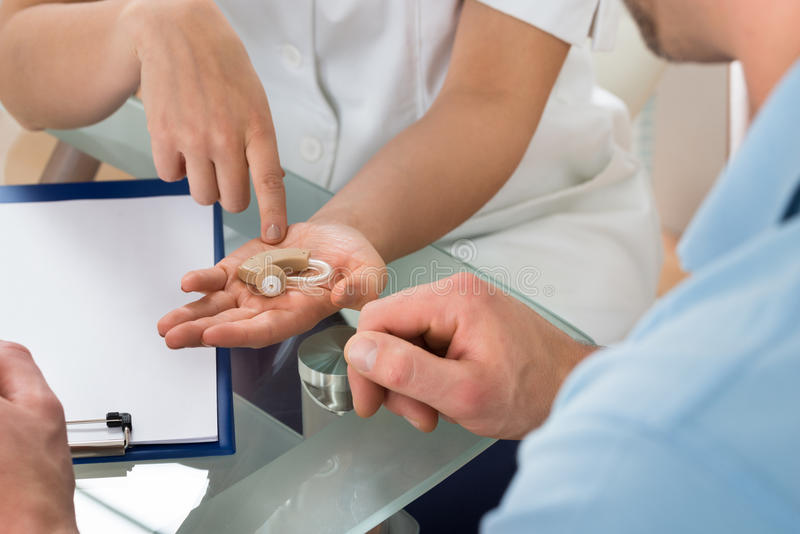 Close-up of doctor showing hearing aid to patient royalty free stock photos