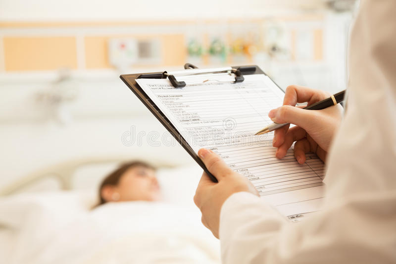 Close up of doctor writing on a medical chart with patient lying in a hospital bed in the background stock photo