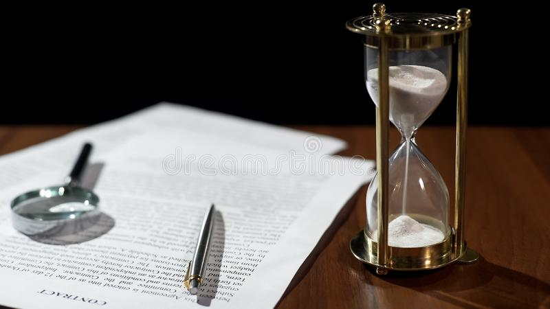 Close-up of document and hourglass on table, contract validity period expiring stock photos