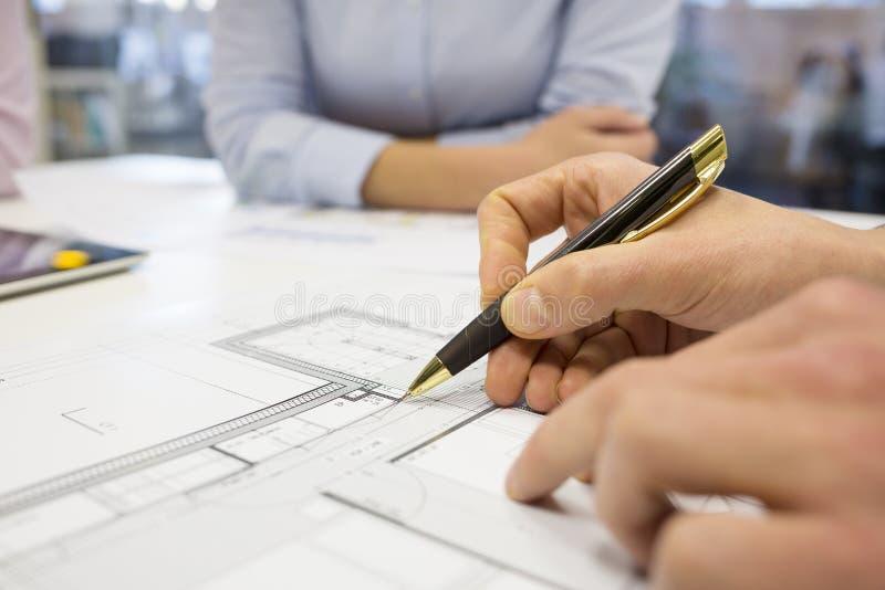Close-up dos arquitetos da equipe que trabalham no projeto de construção no foto de stock royalty free