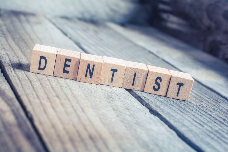 Close up dos blocos de Formed By Wooden do dentista da palavra em um assoalho de madeira imagem de stock