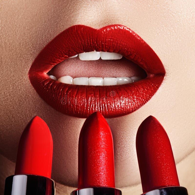 Close-up dos bordos do ` s da mulher com composição do vermelho da forma O tiro macro de bonito compõe nos bordos completos Batom foto de stock royalty free