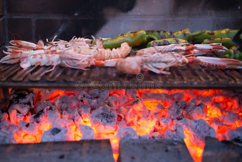 Close-up dos camarões e das pimentas na grade imagens de stock