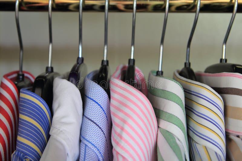 Close up dos colares do men& x27; camisas de s que penduram em um trilho fotografia de stock royalty free
