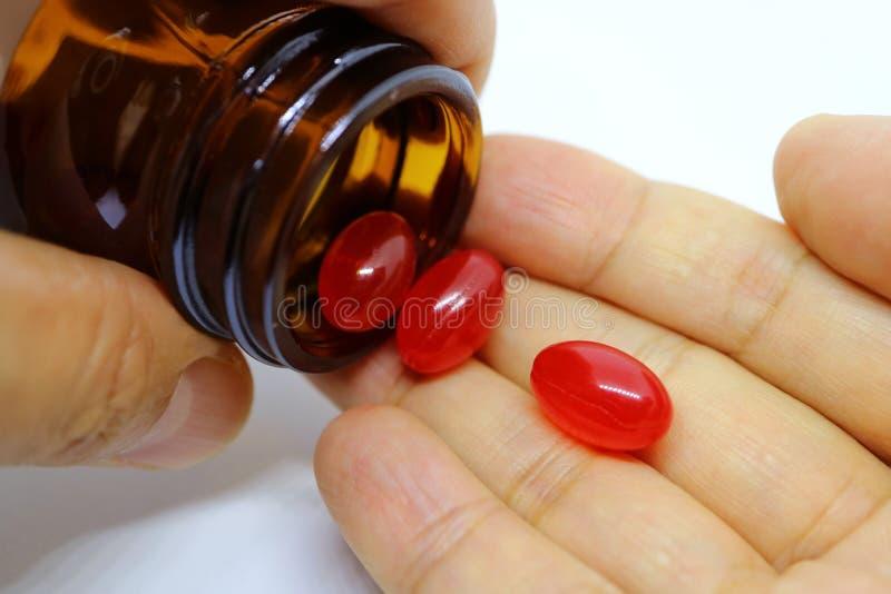 Close up dos comprimidos macios do suplemento ao gel que derramam a garrafa na mão foto de stock