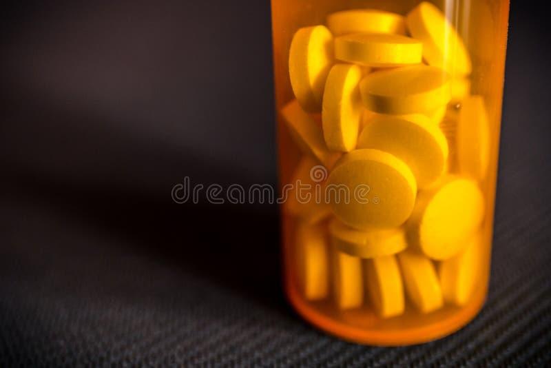 Close-up dos comprimidos ou das tabuletas da medicamentação em uma garrafa de comprimido alaranjada que está em uma tabela preta foto de stock
