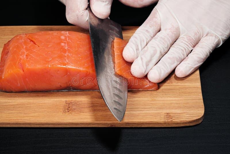 close-up dos cozinheiros das m?os O cozinheiro chefe corta com uma faca um peixe vermelho, salmão fumado em uma placa de corte de imagem de stock royalty free