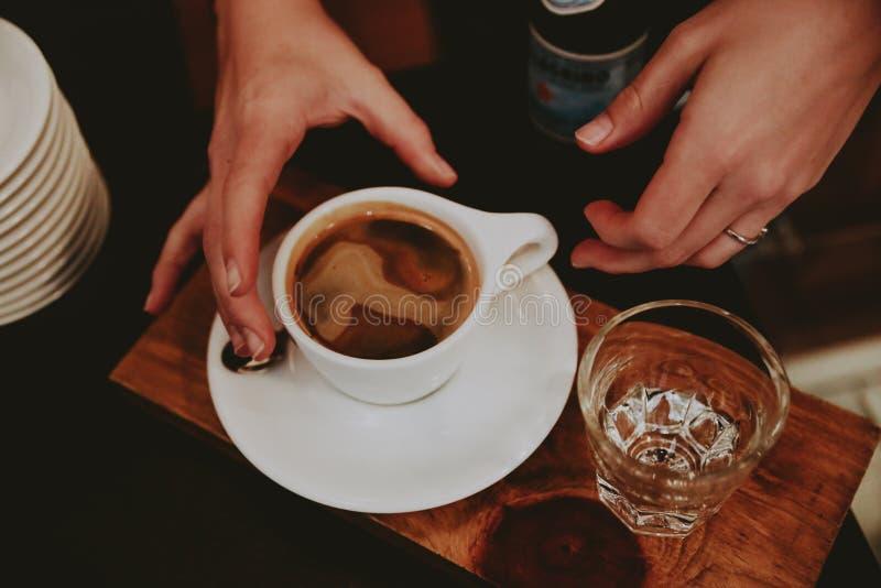 Close up dos dedos da fêmea em uma xícara de café com água gasosa em um trey de madeira imagem de stock