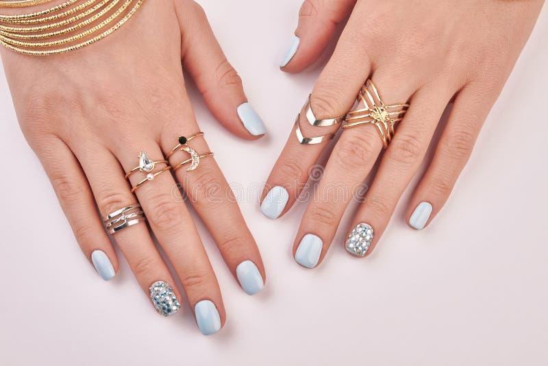 Close-up dos dedos fêmeas com tratamento de mãos e anéis fotos de stock royalty free