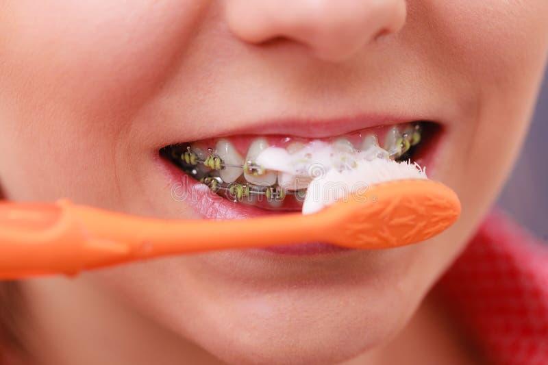 Close up dos dentes da limpeza de escovadela da mulher imagens de stock royalty free
