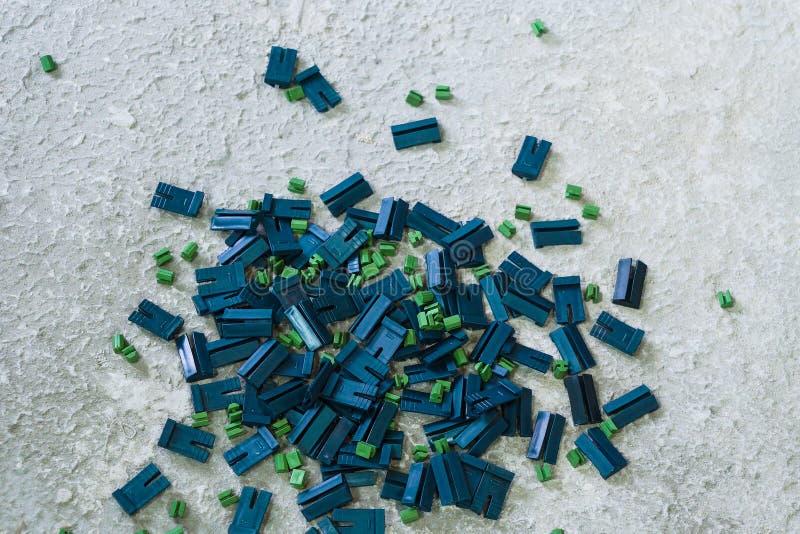 Close up dos grampos plásticos azuis e verdes que encontram-se na superfície áspera fotografia de stock