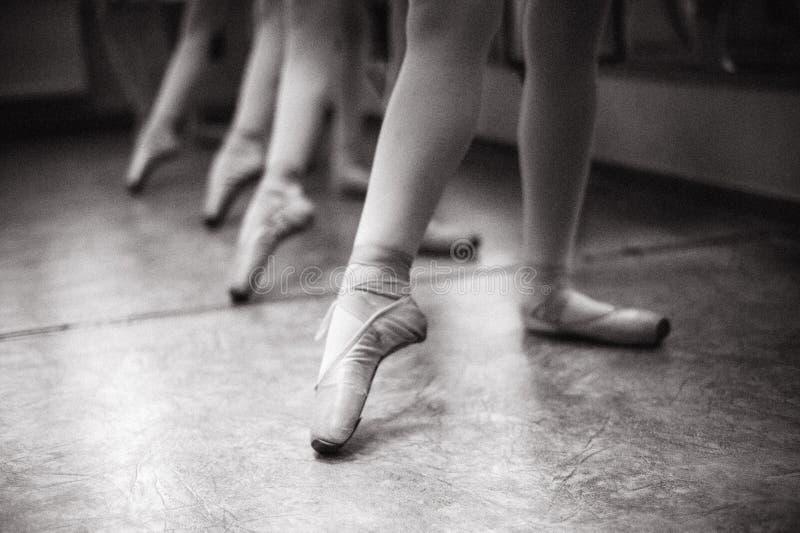 Close-up dos pés da bailarina em sapatas do pointe no salão de dança V imagem de stock