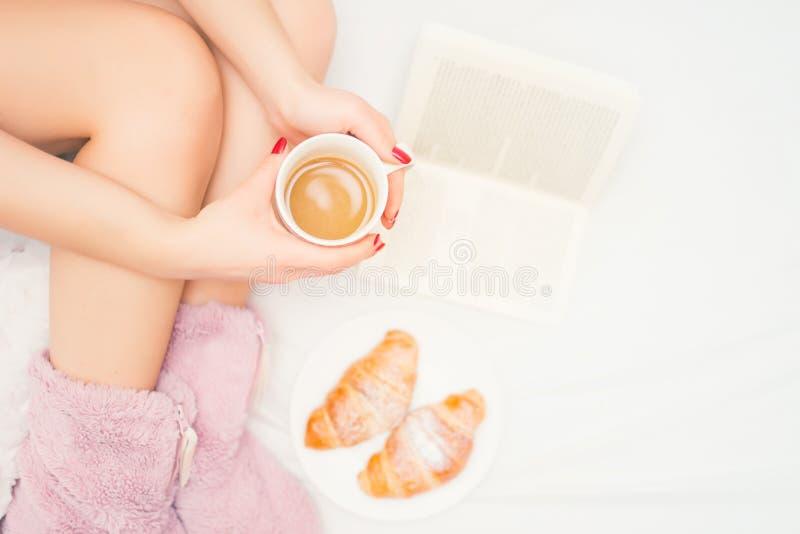 close-up dos pés da mulher com os deslizadores macios que bebem um café e que leem um bom livro fotografia de stock royalty free