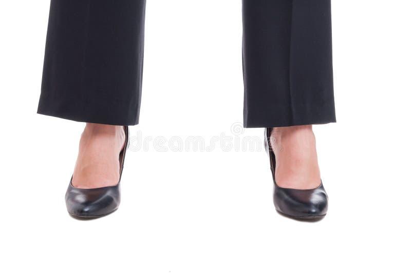 Close-up dos pés da mulher de negócio que vestem as sapatas pretas que estão o spr fotos de stock