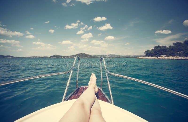 Close up dos pés da mulher, mar no fundo - menina que relaxa em um iate foto de stock