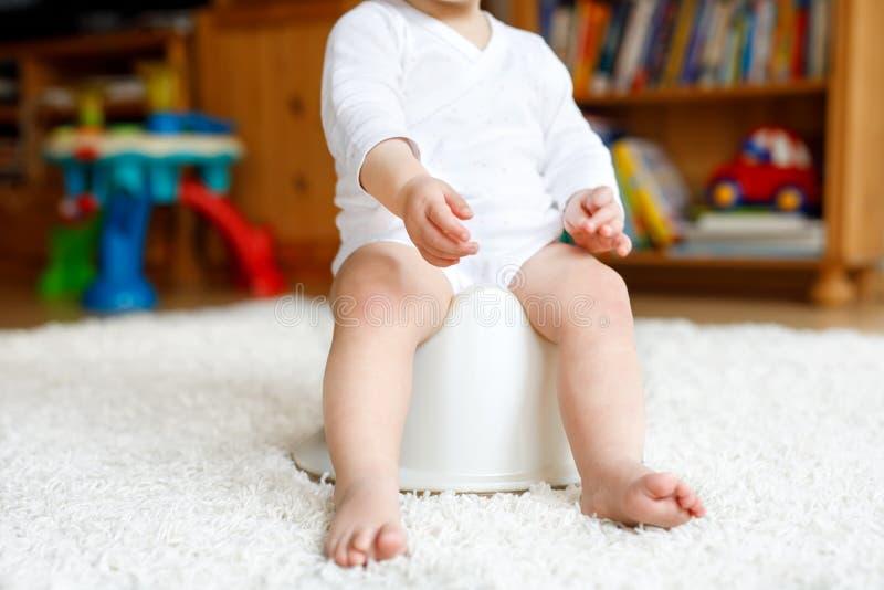 Close up dos pés de 12 meses pequenos bonitos da criança idosa do bebê da criança que senta-se no urinol imagens de stock