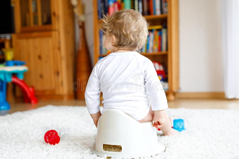Close up dos pés de 12 meses pequenos bonitos da criança idosa do bebê da criança que senta-se no urinol imagem de stock