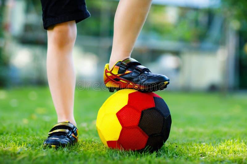 Close-up dos pés do menino da criança com as sapatas do futebol e do futebol em cores nacionais alemãs - preto, ouro e vermelho m imagem de stock