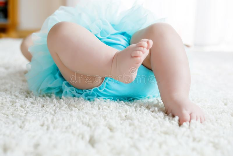 Close up dos pés e dos pés do bebê na saia vestindo do tutu de turquesa do fundo branco imagens de stock