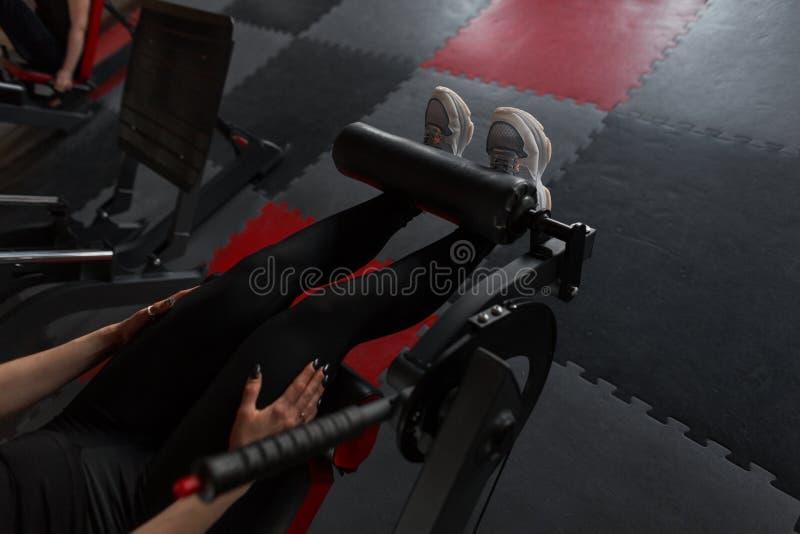 Close up dos pés fêmeas em caneleiras pretas nas sapatilhas brancas A mulher faz exercícios para os pés no gym imagens de stock royalty free