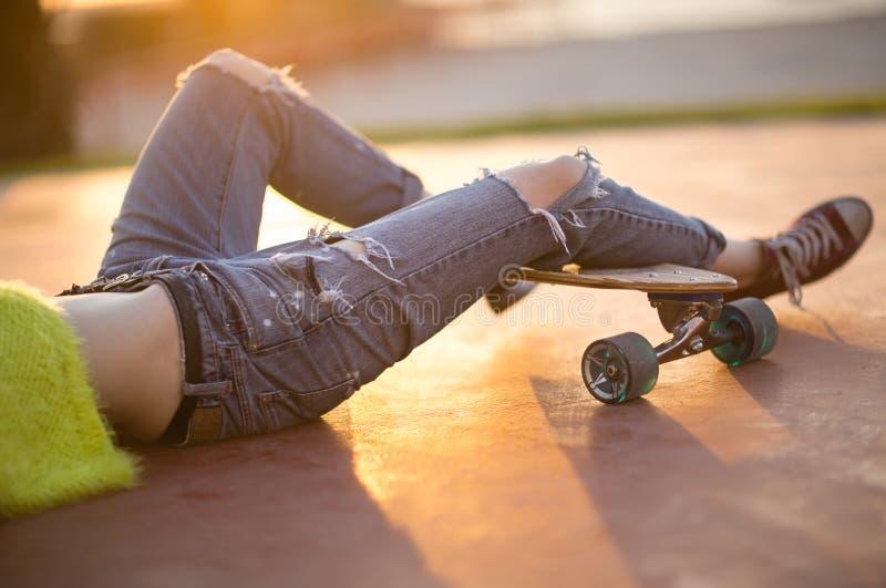 Close up dos pés fêmeas na moda que relaxam em um longboard Forma rasgada das calças de brim Luz solar exterior bonita imagens de stock