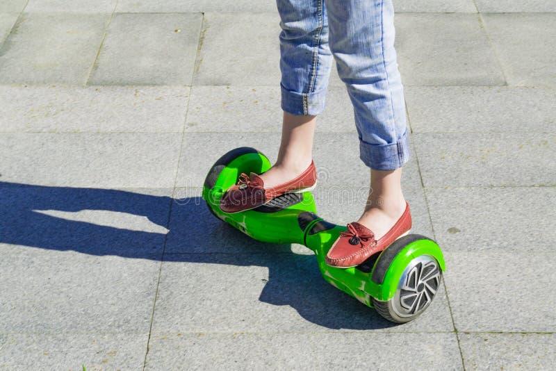 Close-up dos pés fêmeas nas calças de brim que estão em um skate plástico imagens de stock