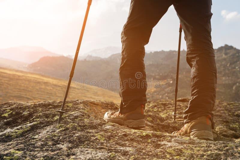Close-up dos pés masculinos em botas trekking com as varas para o nordic que anda na perspectiva das rochas e distante imagem de stock royalty free
