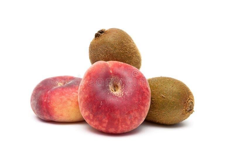 Close-up dos pêssegos e do fruto de quivi em um fundo branco imagens de stock royalty free