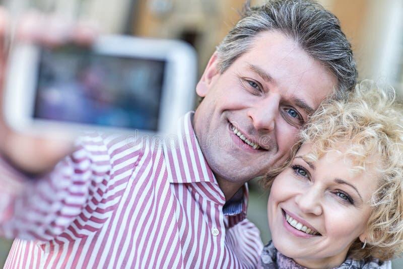 Close-up dos pares de meia idade felizes que tomam o selfie através do telefone esperto foto de stock