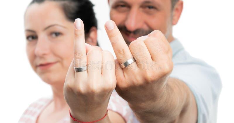 Close up dos pares que apresentam as alianças de casamento fotografia de stock