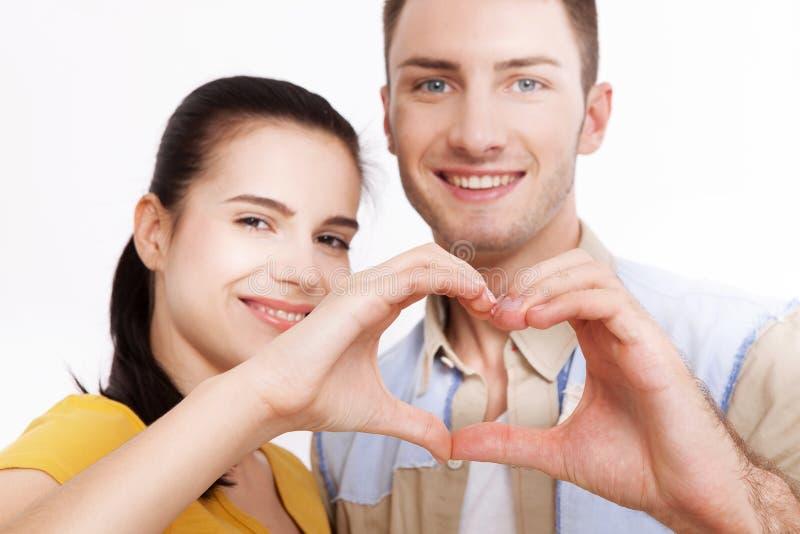Close up dos pares que fazem a forma do coração com as mãos isoladas no fundo branco fotos de stock