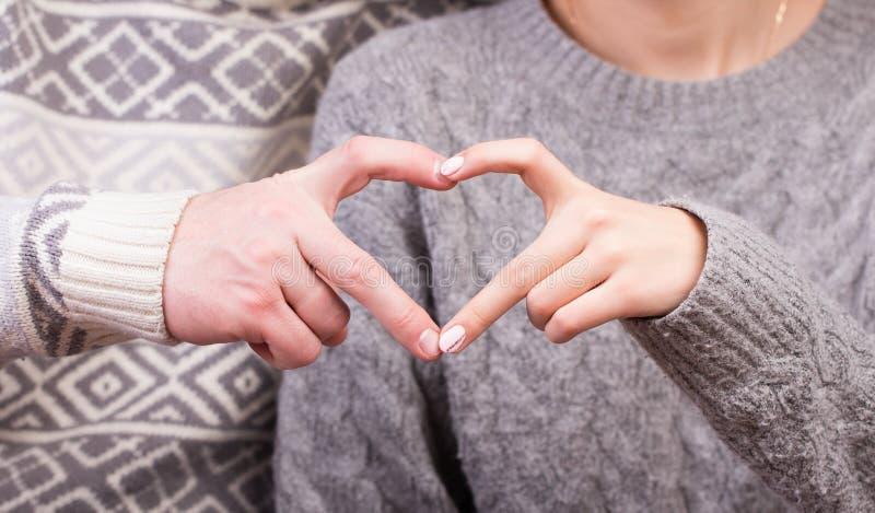 Close up dos pares que fazem a forma do coração com mãos imagem de stock