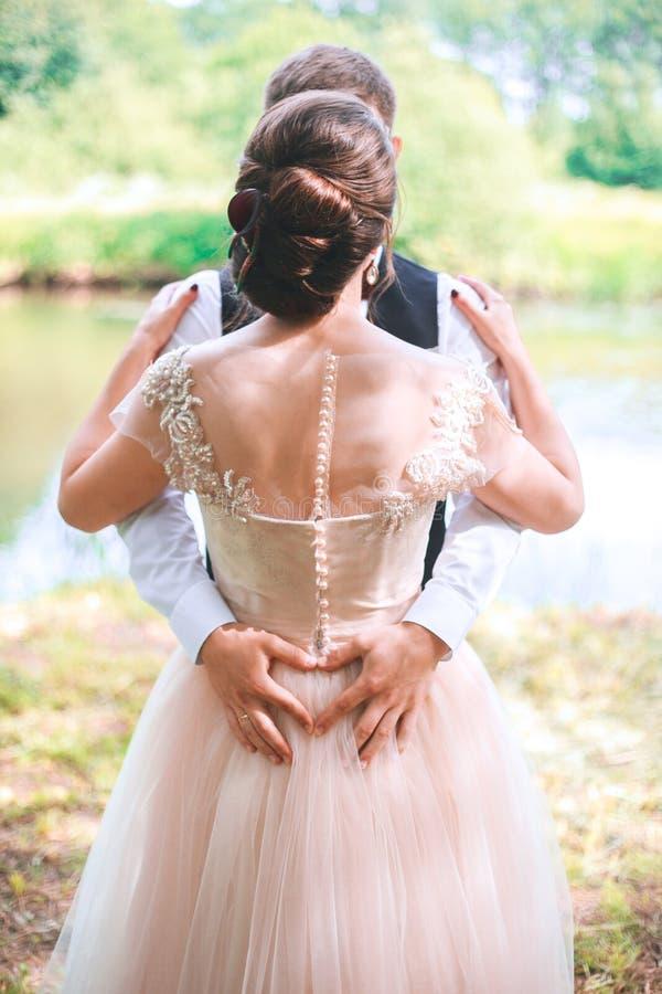 Close up dos pares que fazem a forma do coração com mãos O par do casamento na natureza está abraçando-se Menina modelo bonita no imagens de stock