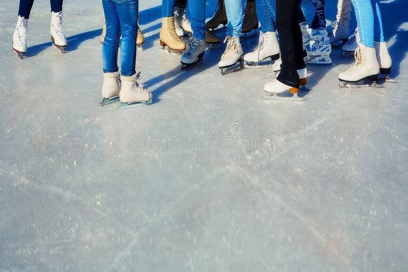 Close-up dos patins dos skateres na superfície do gelo Patim no gelo na empresa dos amigos Arrendamento do patim foto de stock royalty free