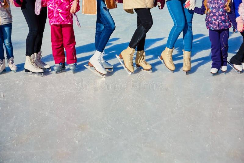 Close-up dos patins dos skateres na superfície do gelo Patim no gelo na empresa dos amigos Arrendamento do patim imagens de stock