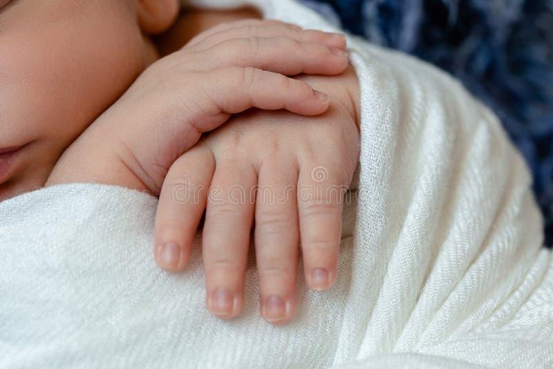 Close-up dos punhos pequenos do bebê O menino recém-nascido de sono sob um geral feito malha branco encontra-se na pele azul fotografia de stock