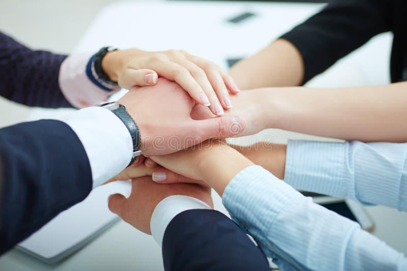 Close-up dos sócios comerciais que fazem a pilha das mãos na reunião equipe imagem de stock royalty free