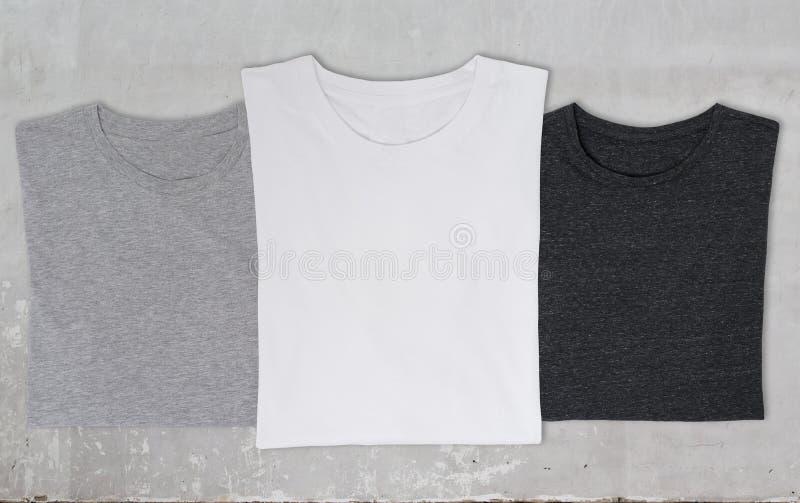Close-up dos três t-shirt (preto, branco e cinzento) imagens de stock