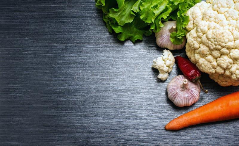 Close-up dos vegetais Couve-flor, alho, cenoura, alface e pimenta vermelha em uma tabela de madeira Parte superior v foto de stock