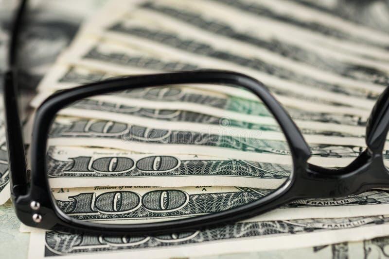 Close up dos vidros que encontram-se no dólar fotografia de stock