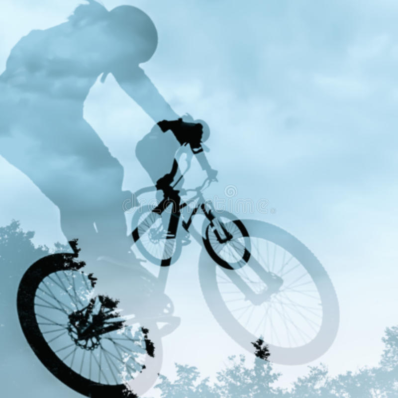 Close-up of double silhouette of unidentified young man doing jump with bmx bike against blue sky. Extrem Sport and risk stock photos