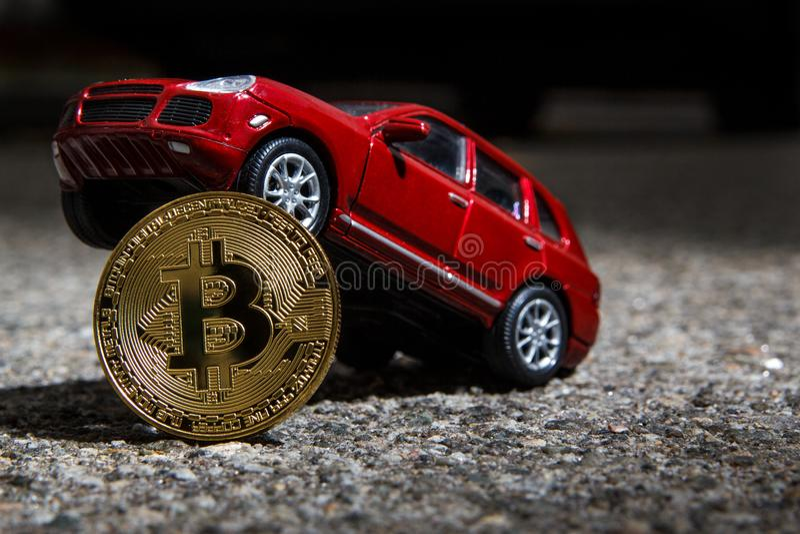 Close up dourado físico da moeda de Bitcoin com o modelo do carro luxuoso vermelho do cruzamento Tema escuro imagens de stock