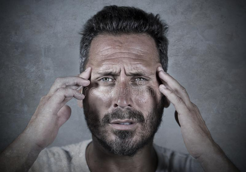 Close up dramatic  portrait of young attractive anxious and depressed man in pain with hands on his head suffering headache and stock image